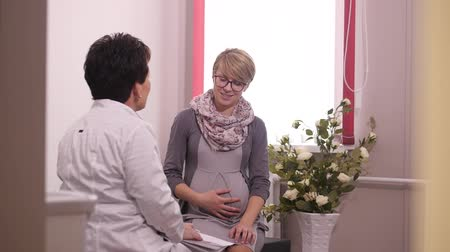 mãos : Pregnant patient listens to the doctor Stock Footage