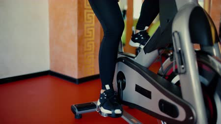 Beautiful brunette girl with long hair rides a bicycle in a gym 4 k Dostupné videozáznamy
