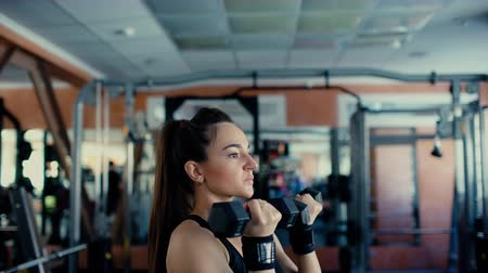 Young sports woman brunette with long hair doing exercises with dumbbells in the gym.