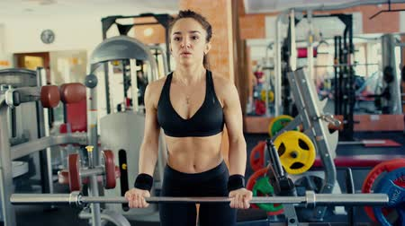 Young sporty woman brunette with long hair lifting barbell bar in gym. Dostupné videozáznamy