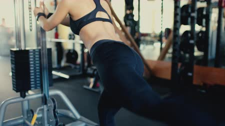 Young beautiful brunette girl with long hair in the gym doing exercise on machine at gym 4 video.