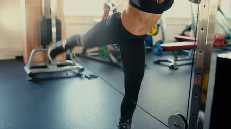 Young beautiful brunette girl wih long hair in the gym doing exercise on machine at gym