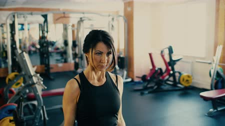 Beautiful sporty brunette middle aged woman lifting barbell bar in gym.