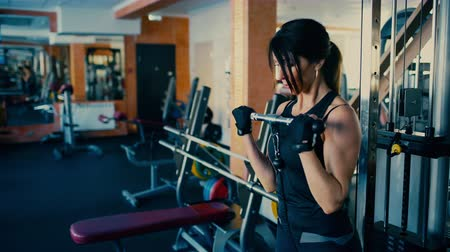 Beautiful sporty brunette middle aged woman blifting barbell bar in gym. Dostupné videozáznamy