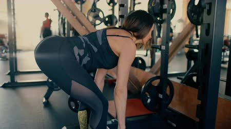 Sexy woman brunette of average years in the gym doing exercises on the squat with a barbell. Dostupné videozáznamy