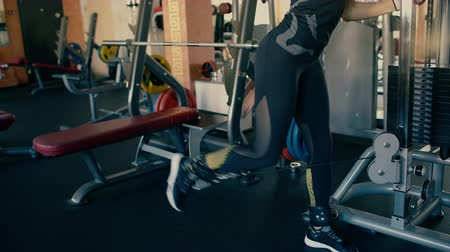 Sporty beautiful brunette middle aged woman training her legs on cable and pulley machine.