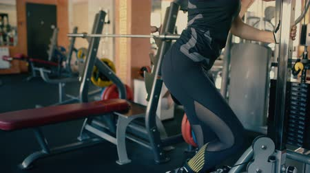 Sporty beautiful brunette middle aged woman training her legs on cable and pulley machine. 4 k Dostupné videozáznamy
