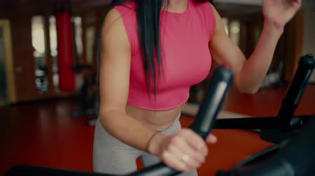elliptical : Athletic young woman working out on stepper machine at the gym, fitness club. Stock Footage