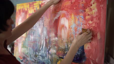 холст : Woman artist painting an abstract painting in the art studio.