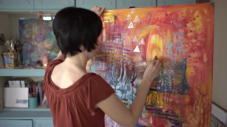 щеткой : Woman artist painting an abstract painting in the art studio.
