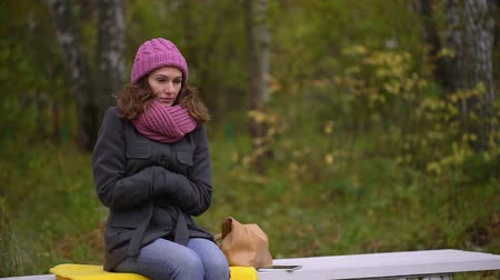 zmrazit : sad beautiful woman freezing in autumn park, cold autumn. She is feeling cold and trying to keep warm. slow-motion