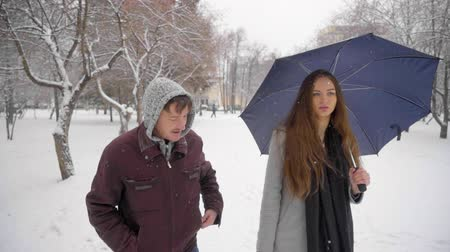 neurotic : Suspicious aggressive man pursues young beautiful woman in the park. fear. fight. danger. Robbery. Crime concept. slow-motion. Man attacking a woman in a winter park.
