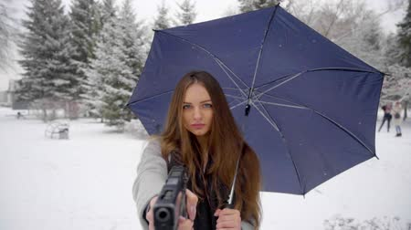 bulletproof : Young woman is pointing a gun at you. Close up of beautiful young woman using gun in winter park. crime criminal. Robbery. Crime concept. close up. Slow motion.