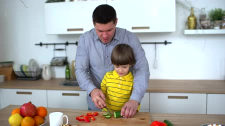 tábua de cortar : Father teaching his son to chop vegetables in the kitchen at home. Cut cucumber. slow-motion. Happy family preparing vegetables together in the kitchen. Fathers Day.