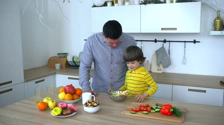 fartuch : Happy father and very cute boy preparing vegetable salad in kitchen. slow-motion. Happy family preparing vegetables together in the kitchen. Fathers Day.