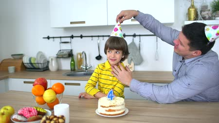 família : Very cute boy celebrating his birthday with a cake & happy father. Fathers Day. Happy birthday of 4 years. Little boy blows out candles on birthday cake at home. Father and son blowing out the candles on a birthday cake together. A happy family.