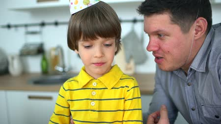 darbe : Very cute boy celebrating his birthday with a cake & happy father. Fathers Day. Little boy blows out candles on birthday cake at home. Father and son blowing out the candles on a birthday cake together. A happy family.