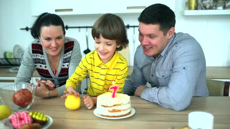 família : Little funny boy in kitchen playing with fruit with mother and father. Very cute boy celebrating his birthday with a cake & happy father and mother. Attractive parents and very cute son is having fun at home in kitchen. happy birthday of 7 years. A happy