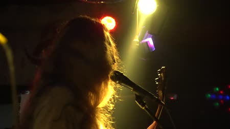 Musician performs solo during concert in night club. Concert rock band performing on stage with singer performer, guitar, drummer. Music video punk, heavy metal or rock group. Slow motion. Dostupné videozáznamy