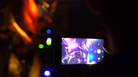 People taking photos or recording video with their smart phones at music concert slow-motion