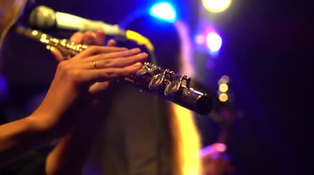 woodwind : close up shot of a woman playing the flute at a rock concert. slow-motion