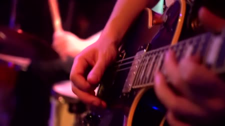 strum : Playing guitar close-up slow motion macro. Guitarist hands pressing chords with fingers on electric guitar. slow-motion