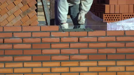 каменная кладка : worker builds a wall of bricks. the builder on a building makes bricklaying. the builder at the construction site makes brickwork. Стоковые видеозаписи