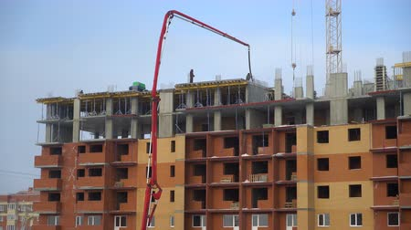 корпус : the construction of a multistory apartment building. Construction workers are pouring concrete floors, construction, concrete pump. Video of Pouring concrete mix from crane pump on top of building