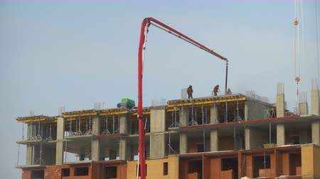 the construction of a multistory apartment building. Construction workers are pouring concrete floors, construction, concrete pump. Video of Pouring concrete mix from crane pump on top of building