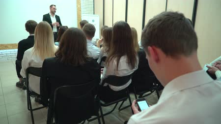 встреча : Student writing the text for work using the smartphone indoors in the audience. View from behind of a group of students in a classroom, listening as their teacher holds a lecture.
