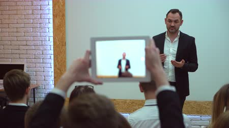 hajtások : View from behind of a group of students in a classroom, listening as their teacher holds a lecture. A man shoots video by tablet at a business meeting, seminar or lecture Stock mozgókép