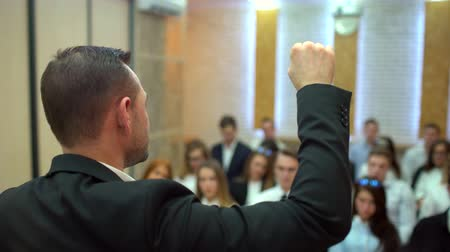 лекция : Lecturer stands in front of an audience. Presentation. Emotional speaker makes a report.  Business People Seminar Conference Meeting Office Training Concept Стоковые видеозаписи