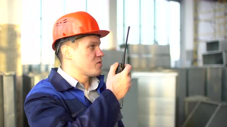 avançar : Engineer builder using a walkie talkie giving instructions at a construction site inside. 4 k