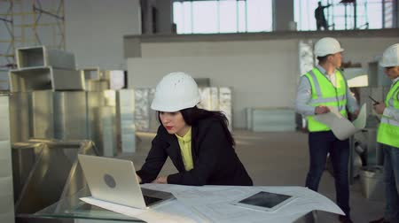 avançar : Construction engineers female or architects wearing had hats use the laptop. Team builders or engineers on background. 4K