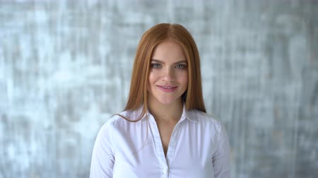 megrémült : Portrait of a smiling redheaded girl. Woman smiling closeup portrait. Young business woman professional looking at camera happy. Portrait of a smiling redheaded girl. 20s. Close up of face woman with red hair. 4 k Stock mozgókép