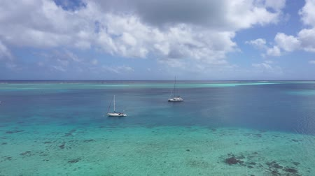 catamaran : High view panning over blue lagoon with few boats anchored, south Pacific ocean, Huahine island, French Polynesia