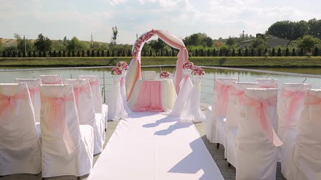 red symbol : decoration for outdoor wedding ceremony. chairs decorating with ribbons. Pink wedding ceremony Stock Footage