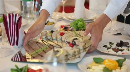placas : waiter puts on a table a gourmet dish of stuffed fish Vídeos