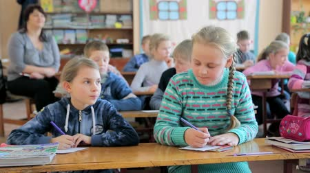 elsődleges : UKRAINE. LVIV. 12.01.2018. First lesson in elementary school. Two girls study at elementary school. Stock mozgókép
