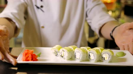 peeled grains : Chefs chef decorates a plate with sushi roles Stock Footage
