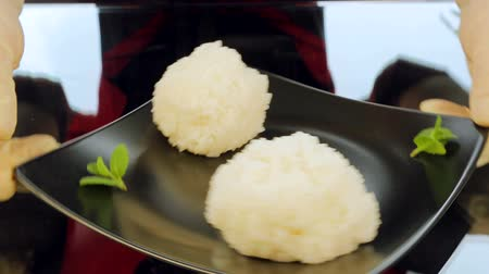 peeled grains : The chef puts a plate of sushi ingredients on the table. Ingredients for sushi, rice and greens