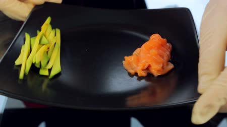 peeled grains : Close up Chef puts a plate of sushi ingredients on the table. Ingredients for sushi, avocado and red fish