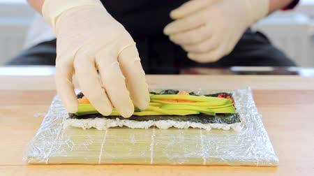 california rolls : The chef puts on avocado in sushi