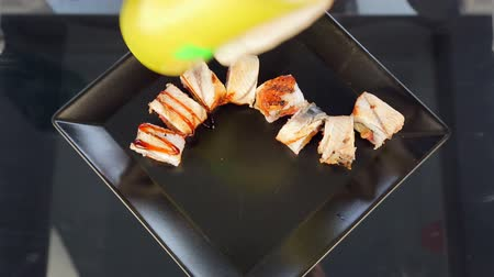 cutting mat : Master sushi rolls puts sushi on a black plate Stock Footage