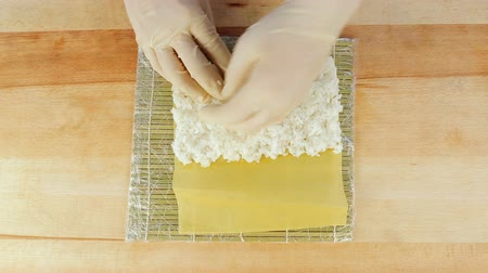 cutting mat : The chef prepares sushi by placing rice on the algae Nuri
