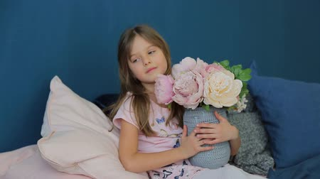 fragrances : Little girl holding a large vase with flowers and plays them in his room on the bed Stock Footage
