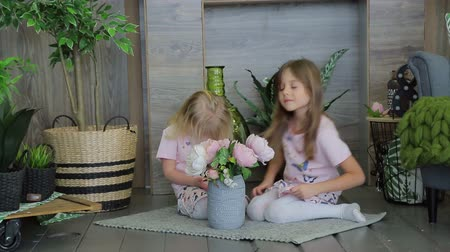 tijolos : Two girls playing in the room decorated with green plants. Two girls sisters having fun