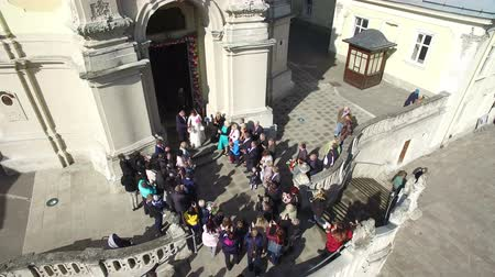 torre sineira : UKRAINE. LVIV. April 2018. Brides come out of the church and throw candies to the guests. Guests meet the newlyweds when leaving the church