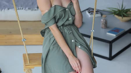 houpačka : Young beautiful girl in a green dress sitting on a swing and showing her tender body Dostupné videozáznamy