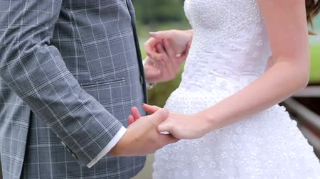 rocznica : Close-up of the Bridegroom takes the brides hand and they embrace.